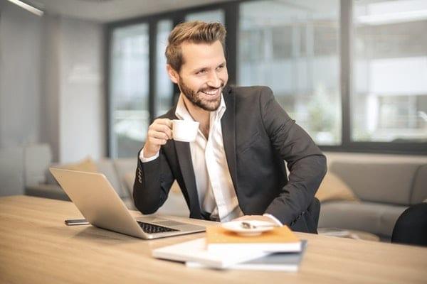 mlady businessman drzi salek kavy u pocitace